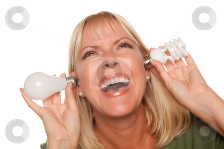 Funny Woman Holding Energy Saving and Regular Light Bulbs to Her stock photo, Funny Faced Woman Holds Energy Saving and Regular Light Bulbs to Her Ears Isolated on a White Background. by Andy Dean