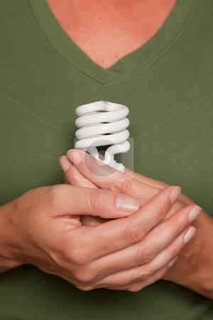 Female Hands Holding Energy Saving Light Bulb stock photo, Female Hands Holding Energy Saving Light Bulb Against Green Shirt. by Andy Dean