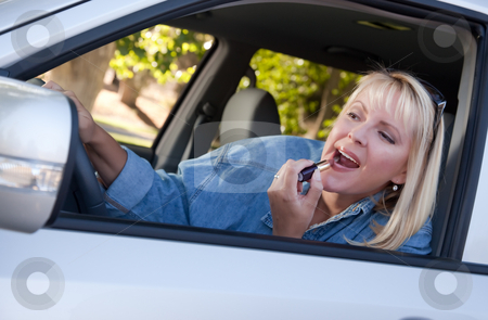 Woman Putting on Lipstick While Driving stock photo, Attractive Woman Putting on Lipstick While Driving. by Andy Dean