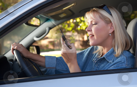Woman Text Messaging While Driving stock photo, Attractive Blonde Woman Text Messaging on Her Cell Phone While Driving. by Andy Dean