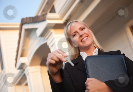 Real Estate Agent Handing Over Keys to New Home stock photo, Female Real Estate Agent Handing Over Keys in Front of Beautiful House. by Andy Dean
