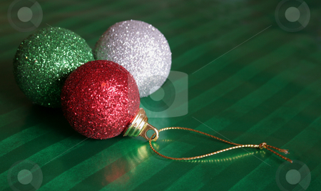 Three shiny Christmas baubles stock photo, Three shiny Christmas baubles sitting on green wrapping paper. by Chris Hill
