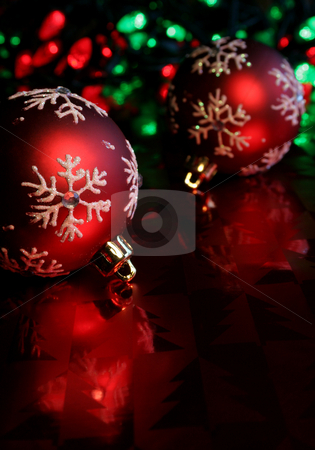 Red Snowflake Baubles stock photo, Two red christmas baubles illuminated on glossy red paper. by Chris Hill