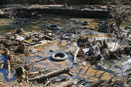 Poluted waters stock photo, Polluted river bed full of junk that should not be by Jack Schiffer
