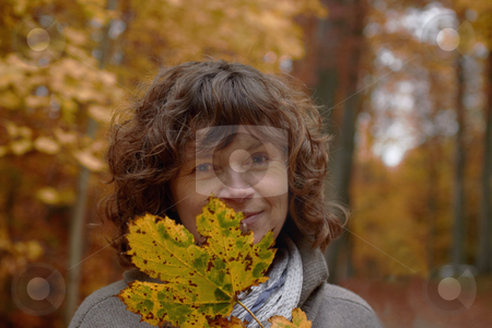 Autumn - middle aged woman looking at you behind a maple leaf stock photo, Autumn - middle aged woman looking at you from behind a maple leaf by Phillip Dyhr Hobbs