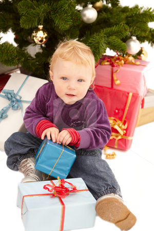 Cute little girl opening christmas gifts stock photo, Cute little girl opening christmas gifts under a tree by Phillip Dyhr Hobbs