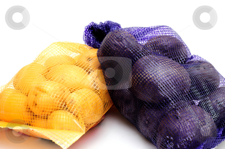 Exotic Potatoes stock photo, Dutch yellow and Peruvian purple potatoes in mesh bags that match the color of the potato isolated on a white background by Lynn Bendickson