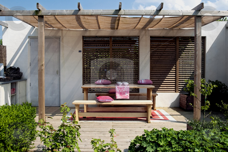 Wooden patio in garden stock photo, Simple outside living place with wood elements and red touch by Wino Evertz