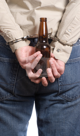 Arrested For Drinking stock photo, A concept image of a man arrested for drinking a driving featuring a man holding a beer bottle with his hands cuffed behind his back by Richard Nelson