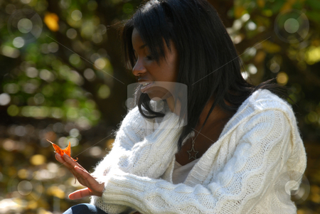 African-American woman gazes at a leaf stock photo, African-American woman gazing at the colors of a fall leaf by Hasan Shaheed