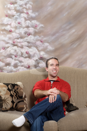 Metrosexual Christmas Man stock photo, A smiling metrosexual man sitting on a sofa in front of a hand painted christmas tree by Richard Nelson