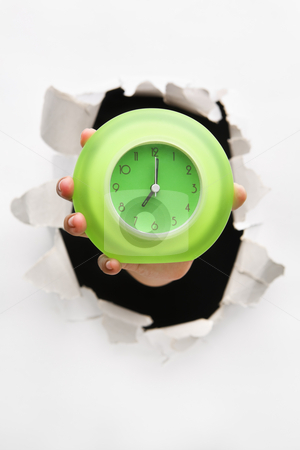 Hand breakthrough wall holding green clock stock photo, Hand breakthrough wall holding green clock - one of the breakthrough series by Rudyanto Wijaya