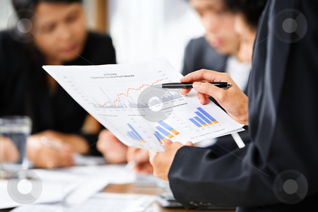 Examining graphs with other people on background stock photo, Businesswoman examining graphs with other working people on background by Rudyanto Wijaya