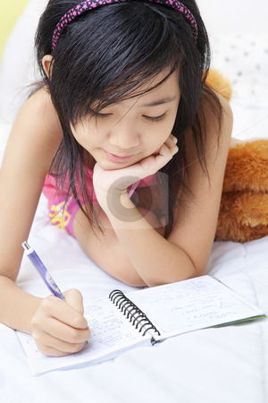 Little girl writing her diary stock photo, A little girl writing her diary in her bedroom by Rudyanto Wijaya