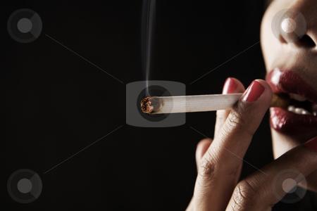 Woman smoking on dark area stock photo, Woman smoking on dark area by Rudyanto Wijaya