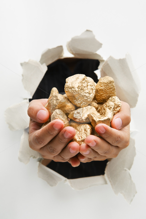 Hand breakthrough wall holding lumps of golden nuggets stock photo, Hand breakthrough wall holding lumps of golden nuggets means breaktrhough in finance or similar things - one of the breakthrough series by Rudyanto Wijaya