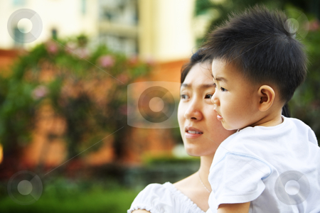 Mother and son waiting father to come home stock photo, Mother and son waiting father to come home in apartment's garden area in the afternoon by Rudyanto Wijaya