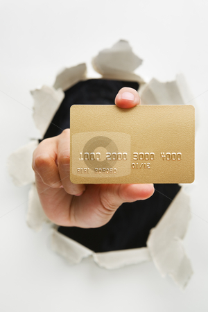 Breakthrough in credit card innovation stock photo, Hand holding gold credit card through cracked wall means breakthrough in credit card innovation - one of the breakthrough series by Rudyanto Wijaya