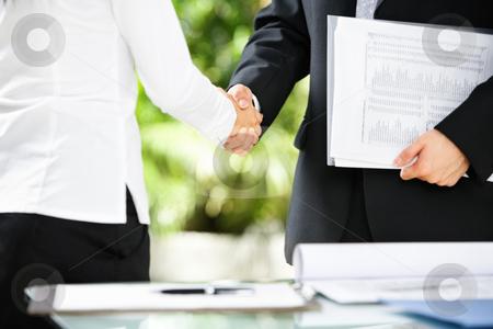 Handshake between businessman and businesswoman stock photo, Handshake between businessman and businesswoman in a meeting by Rudyanto Wijaya