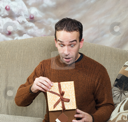 Christmas Surprise stock photo, A young man looks surprised at what he sees for his Christmas present by Richard Nelson