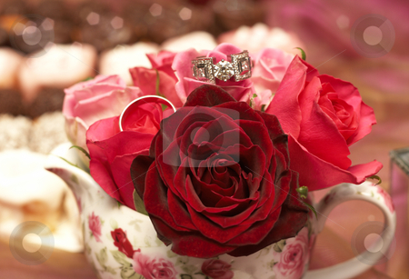 Bouquet of roses with wedding rings stock photo, Small bouquet of red and pink roses in a vase with two wedding rings on top. Very shallow depth of field, macro shot by Elena Weber (nee Talberg)
