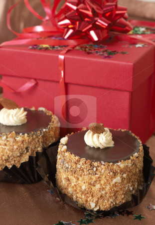 Miniature chocolate cakes and gifts stock photo, Miniature chocolate meringue cakes with cream and almonds and red gift boxes in the background by Elena Weber (nee Talberg)