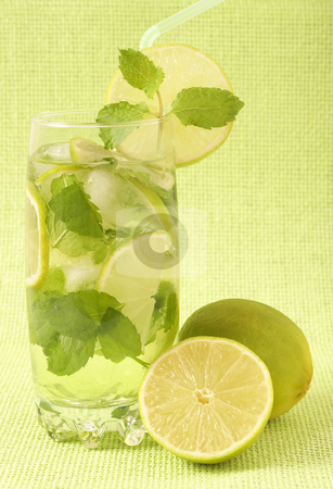 Mojito cocktail on green background stock photo, Mojito cocktail with lime, mint leaves and ice on green mesh background by Elena Weber (nee Talberg)