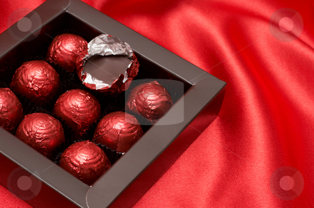 Chocolate Valentines truffles in red paper stock photo, Chocolate Valentines truffles wrapped in red paper on silk material background by Elena Weber (nee Talberg)