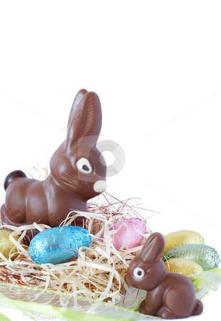 Colorful wrapped chocolate Easter eggs stock photo, Assortment of chocolate Easter eggs wrapped in colorful paper with chocolate bunnies on straw by Elena Weber (nee Talberg)