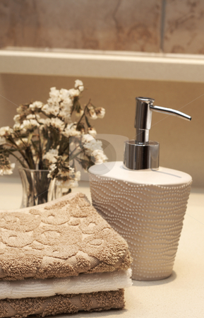 Stack of towels and soap in the bathroom stock photo, Stack of white and brown towels and bottle of liquid soap with some dry flowers in the bathroom by Elena Weber (nee Talberg)