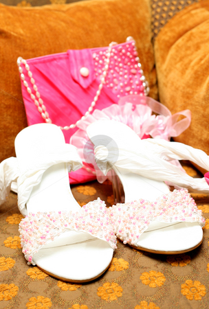 Bridal shoes with beads and bag stock photo, White bridal shoes adorned with pink, white and silver beads with a pink bag and garter in the background lying on brown chair by Elena Weber (nee Talberg)