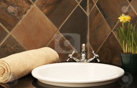 Modern bathroom interior stock photo, Modern bathroom interior with a wash basin, beige rolled up towel and bright yellow daffodil flowers by Elena Weber (nee Talberg)