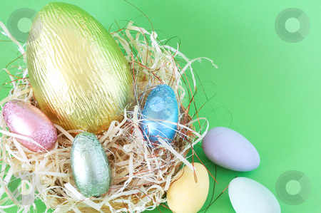 Chocolate Easter eggs in straw stock photo, Chocolate Easter eggs in straw on green background by Elena Weber (nee Talberg)