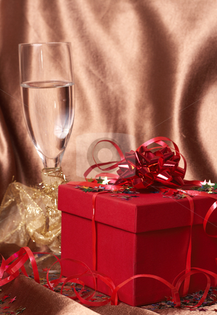 Red gift box with bows and stars stock photo, Party theme - red gift box with bows and stars with a glass of champagne on golden silk background by Elena Weber (nee Talberg)