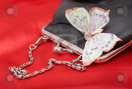 Black purse with butterfly on Valentines stock photo, Black purse with colorful butterfly shot on red silk background on Valentines day by Elena Weber (nee Talberg)