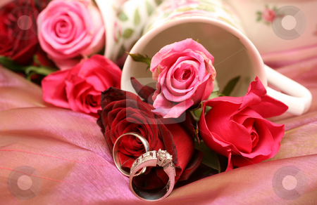 Bouquet of roses with wedding rings stock photo, Small bouquet of red and pink roses in a vase with two wedding rings. Very shallow depth of field, macro shot by Elena Weber (nee Talberg)