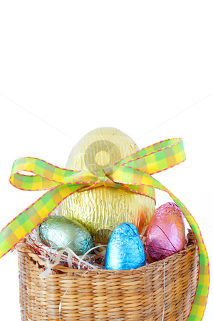 Easter chocolate eggs stock photo, Assortment of chocolate Easter eggs wrapped in colorful paper in straw basket isolated on white background by Elena Weber (nee Talberg)