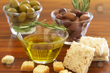Two jars of green and black olives and croutons stock photo, Two jars of green and black olives with stick of rosemary, croutons and slices of wholewheat bread on wooden table background by Elena Weber (nee Talberg)