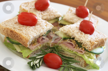 Tasty club sandwich on wholewheat bread stock photo, Tasty club sandwich with green lettuce, cheese, smoked ham and wholegrain mustard on wholewheat bread with rosemary and tomatoes on white plate by Elena Weber (nee Talberg)