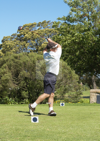Golfer hitting the ball off the tee box stock photo, Senior golfer hitting the ball off the tee box. Peg flying past the left leg. Nice summer day by Elena Weber (nee Talberg)