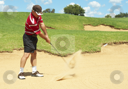 Senior golfer playing golf from sand bunker stock photo, Senior male golfer playing golf from the sand bunker on a beautiful summer day by Elena Weber (nee Talberg)