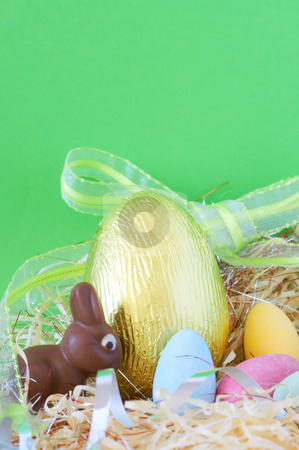 Colorful wrapped chocolate Easter eggs stock photo, Assortment of chocolate Easter eggs wrapped in colorful paper with bunny in straw by Elena Weber (nee Talberg)