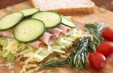 Tasty open sandwich on wholewheat bread stock photo, Tasty open sandwich with green lettuce, grated cheese, smoked ham and cucumber on wholewheat bread with rosemary and tomatoes on chopping board by Elena Weber (nee Talberg)