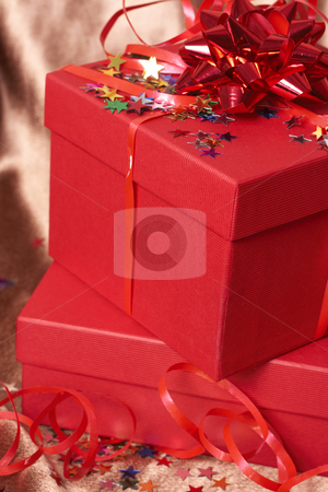 Red gift boxes with bows and stars stock photo, Red gift boxes with bows and stars on golden silk background by Elena Weber (nee Talberg)