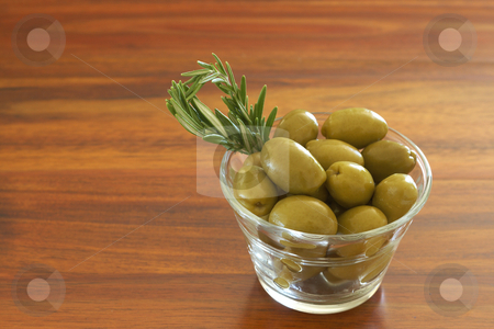 Single jar of green olives with rosemary stock photo, Single jar of green olives with stick of rosemary on wooden table background with copy space by Elena Weber (nee Talberg)