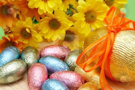 Colorful wrapped chocolate Easter eggs stock photo, Assortment of chocolate Easter eggs wrapped in colorful paper with spring flowers in the background by Elena Weber (nee Talberg)