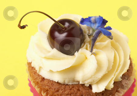 Miniature vanilla cupcake with cherry stock photo, Miniature vanilla cupcake with icing, fresh cherry and blue flower on yellow background by Elena Weber (nee Talberg)
