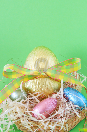 Colorful wrapped chocolate Easter eggs stock photo, Assortment of chocolate Easter eggs wrapped in colorful paper in the basket with straw by Elena Weber (nee Talberg)