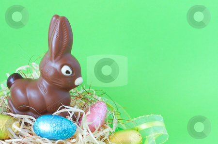 Easter chocolate eggs and bunny stock photo, Assortment of chocolate Easter eggs wrapped in colorful paper and bunny in straw by Elena Weber (nee Talberg)
