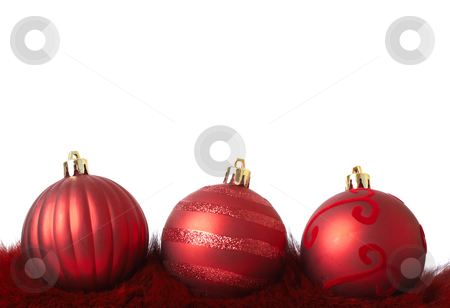 Red Christmas baubles on fur stock photo, Three red Christmas baubles on fur isolated on white background with copy space. Shallow depth of field by Elena Weber (nee Talberg)